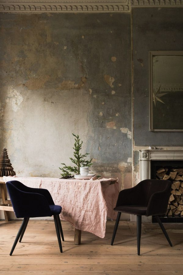 wabi sabi interior idea with shabby gray walls coffee table with light rose tablecloth black velvet chairs wood floors