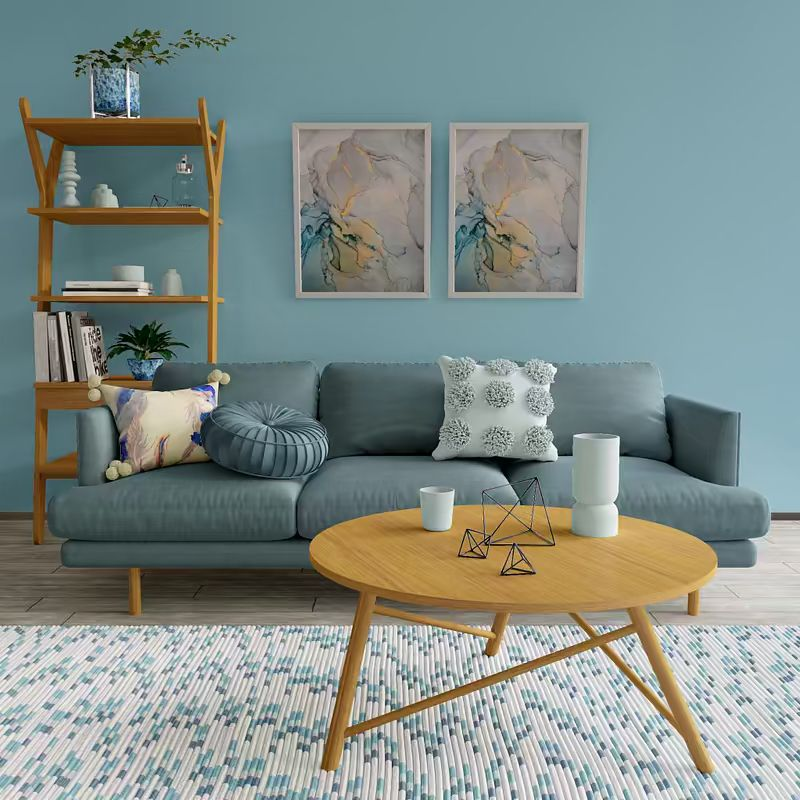 warm blue sofa in mid century style round top light wood coffee table light wood bookshelves fancy area rug light blue walls