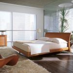 Contemporary Brown Bedroom Chair In Modern Style On Beige Fur Rug Including Wooden Floor Also Lamps Desk The Bedside And Wide Glass Window View City