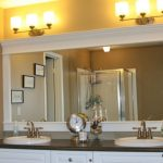 classic Bathroom decor With White Picket Rectangular Mirror Body With Image Frames Dangle On The Brown Wall As Properly Wall Lamps on The Mirror plus wall Clock On The Vanity Double wash basin