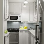Fancy Small Galley Kitchen Design With Track Lighting Also White Wooden Cabinet Plus Microwave Ideas