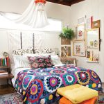 White painted wooden wall dark wooden ceiling white curtain unique pendant lamp colorful patterned bedspread colorful patterned rug colorful cushion wooden framed wall accessories wooden bookshelves
