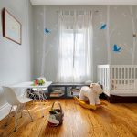 Adorable Nursery Room With Cute White Low Crib Also Elegant Nature Painting On The Wall With Exxentruc Wooden Floor Also Beautiful Ship Rocking Chair For Minimalist House Deisign
