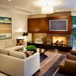 amazig masculine living room with golden accent also wonderful buil-in wall media with large painting also warm rug in laminate flooring concept