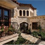 amazing mediteranian house with interesting stone wall and gorogeus iron fence with sturdy teak wooden windows