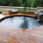 amazing small swimming pool with round design and magnifceint wooden pool deck and gorgeous stone waterfall surrounded with lush and green forest