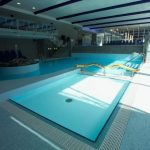 awesome indoor swimming pool with beige ceramic flooring wooden roof