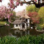 beautiful pond amazing pink flower wonderful scenery white concrete white swan statue small house with straw roof cane doll wearing hat and bring ukulele brown framed door  iron windows