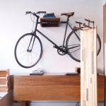 Bicycle With Black Frame And Dark Brown Saddle Brown Wood Table Brown Bookshelf Light Brown Shelf White Painted Wall A Pile Of Books Handmade Wood Craft