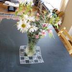 black painted chalk table light wooden varnished chairs light wooden varnished floor colorful striped rug flowers in the glass pot creame painted wall