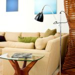 Black Unique Cruvy Floor Lamp Laminated Wooden Flooring White Wall Round Glass Side Table Cream Sofa Green Pillow Dark Purple Pillow Cream Rug Blue Gradiant Wall Decorations