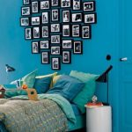 blue wall hardwood flooring blue door with white doorknob blue and turquoise bedding set white round table black table lamps yelllow pillow hear-shaped photos wood bed table
