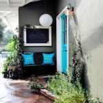 bold turquoise door with white frame black lantern beautiful white hanging lamp black chair charcoal black wall turquoise cushions concrete flooring black welcome mat white ceiling