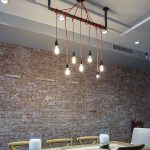 brick wall white painted ceiling white painted hanging pipes red cabled pendant lamp small downlights rustic wooden dining table rustic wooden dining chair