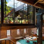 brick wall wooden varnished floor wooden varnished stair open glass panel round wooden dining table wooden varnished storages green dining rug industrial modern loft cozy living space