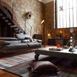 bricked wall wooden varnished wall beautiful floor rug gray leathered sofa wheeled coffee table large metal framed window industrial floor lamp industrial design style room