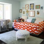 bright colored wall small gray crib white cute stool patterned orange and white daybed patterned light gray rug red trash bin beautiful baby nursery room