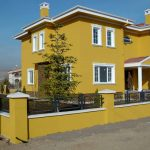 bright yellow painted wall exterior white painted window frame two floored house black small fence front porvh well groomed garden green plantations color for house exterior