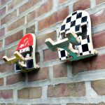 broken skateboard with chessboard design old skateboards with red lime green black colors in it and some scratches funky skatehook wall hook double-headed hook raw brick wall
