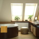 brown ceramic tile floor wooden bathroom counter wooden bathroom cabinets rattan stool wooden framed mirror sloping skylighted ceiling round bathtub bright and warm bathroom