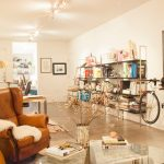Brown Leather Armchair Grey Ceramic Flooring White Wall Railing Lamps Glass Table Steel Bookshelf White Ceiling Gold Scounce Brown Desk White Bicycle White Patterned Vase