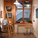 brown wood windows raw brick wall white wall wood easle black steel easle black framed paintings brow grey patterned ceramic flooring black cabinet dark brown table light brown office chair
