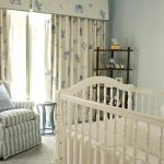 comfortable blue-white stripped armchair animal patterned cream curtain light blue small table white wooden crib light blue wall wood shelf white bed sheet diagonal patterned floor