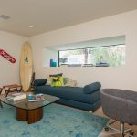 creame painted wall creame painted ceiling blue patterned floor rug blue sofa wooden stool wooden with glassed surface coffee table wheeled chair contemporary villa design in Malibu
