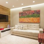 creame painted wall white furry rug white sofa colorful armchair white storages colorful abstract painting creame painted ceiling wooden wall Vila Mariana Residence in Brazil by Cristiane Bergesch
