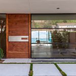 creame painted wall wooden pivot door glassed large window creame painted ceiling stony large footpath modern house facade contemporary villa design in Malibu