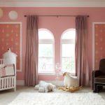 cute pink wall white framed windows white fur rug ceramic flooring pink curtain dark brown armchair ahite crib white ceiling animal doll white bed sheet