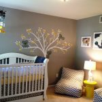 cute stripped whit and black chair yellow round table white table lamp grey wall white ceiling white crib white tree and grey koala mural brown carpet white framed pictures