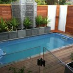 encanting small swimming pool with elegant granite base also wonderful hardwooden deck with gorgeous wood fencing also elegant small garden