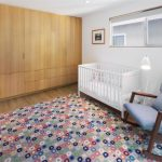 exciting nursery room gorgeous grey rocking chair interesting square pattern carpet large wooden wall panel elegant white crib laminate flooring concept