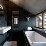 extravagant black bathroom with gorgeous iron tower racks and elegant white long bathtub also wonderful white sink with ample natural light from window