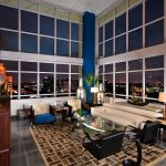 extravagant masculine living room with wonderful night city view also interesting cream leather sofa and black armchairs with gorgeous wooden cabinet with square pattern rug in glossy tiling