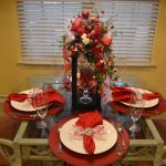 glass dining table red table mat white ceramic plate painted wooden armchair red napkin drinking glass light yellow painted wall beautiful synthetic flower bucket glass candlestick
