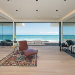 glassed sliding door light wooden floor mediterranian patterned rug brown leathered relaxing chair creame painted ceiling beautiful ocean view contemporary villa design in Malibu