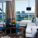 gorgeous masculine living space with cozy white sofa and goroegus large window glass with amazing city life view also warm fur rug with palm pot in corner with black arc lamp for modern house design