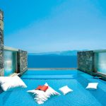 gorgeous swimming pool idea with floating white cushion also magnificent wall stone divider overlooking sea view