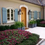 gorgesous country side house with blue colored exterior also beautiful flower garden and ravishing wall lamp in hardstone walkaway design