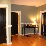 gray painted wall wooden varnished floor black painted table white painted ceiling black pianted main door black painted interior door white painted door frame