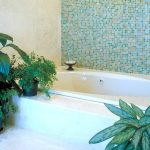 green mozaic tile wall marble tiled wall drop in white bathtub lpotted leafy plants potted ferns bathroom plant options green bathroom idea beautiful bathtub area