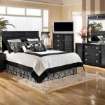 hardwood flooring black dresser table black framed mirror black cabinet cream rug cream wall black side table white table lamp white curtain wide white window purple vase white and black bedding set