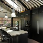 interesting black and gray kitchen accent with exotic white pendants also interesting iro barstools with large framed window and concrete countertop with undermount sink