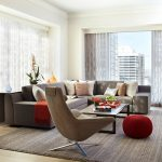 interesting masculine living room with gorgeous dark read round chair also gorgoeus brown rustic sofa and wide white curtains with tribal motif rug in laminate flooring
