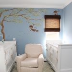 light blue painted wall with painted picture double white cribs patterned creame rocking chair white painted ceiling patterned floor rug cute baby nursery room