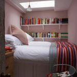 light pink painted wall white wooden small bed white hanged bookshelves wooden varnished cabinet white bedsheet colorful striped bedspread small pendant lamp ironed armchair floral cushion