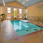 magnificen small indoor swimming pool with gorgeous blue tile base and magnifceint brick wall and grabiet paving with exquisite armchair for class house style