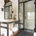 magnificent bathroom design with elegant white tile walling also large black framed mirror also uniqe washing stand furniture in granite flooring